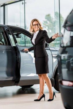 Happy female car dealer opening car in showroom stock vector