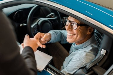 cropped shot of female car dealer passing car dealership contract to smiling adult man in showroom