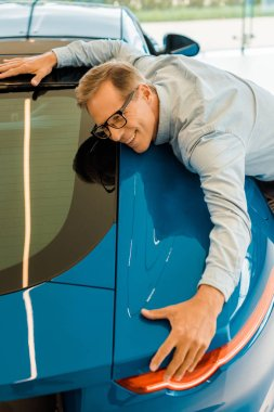 happy adult man embracing luxury sport car in showroom