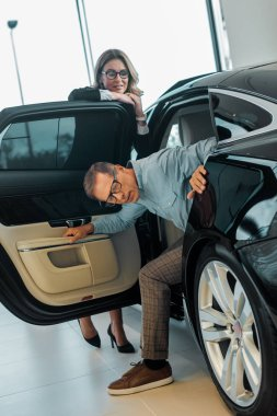 adult man checking luxury car with female car dealer at showroom