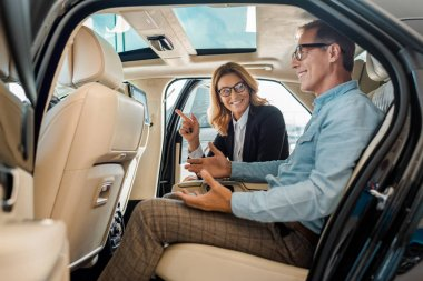 side view of happy adult man and female car dealer sitting on back seat of luxury car and talking