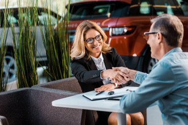 happy adult customer and female car dealer shaking hands in showroom