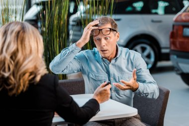 shocked adult customer and female car dealer sitting in showroom