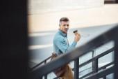 Fotografie Selektivní fokus hezký středního věku podnikatel pití kávy z papírového kelímku na ulici