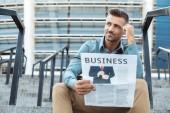 zamyšlený usmívající se muž držící obchodní noviny a hledat dál zatímco sedí na schodech