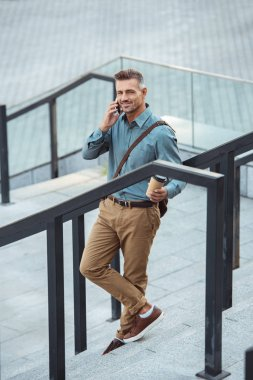 high angle view of smiling man holding coffee to go and talking by smartphone on stairs