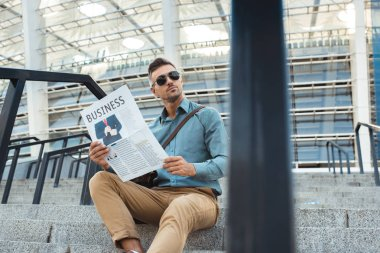 handsome man in sunglasses holding business newspaper and looking away while sitting on stairs