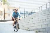 hezký středního věku podnikatel v brýle, jízdě na kole a koukal na ulici
