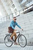 Fotografie handsome middle aged businessman in sunglasses riding bike on street