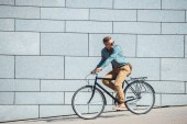 Fotografie side view of stylish middle aged man riding bicycle and looking over shoulder on street
