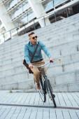 Stylový středního věku muž v brýle, jízda na kole na ulici