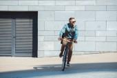 Stylový středního věku muž v sluneční brýle jízda kole a koukal na ulici
