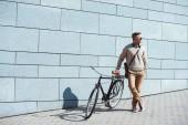 Fényképek stílusos középső férfi kerékpár állva, és keres el utcában