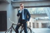 pohledný podnikatel sedí na kole a mluví o smartphone na ulici