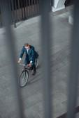 Fotografie vysoký úhel pohled podnikatel v oblasti formálního oblečení, jízda kole a koukal na ulici