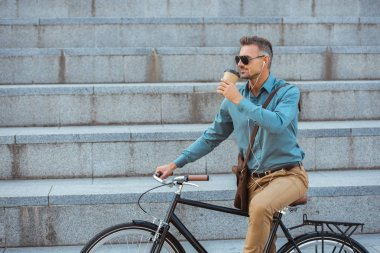 handsome man in sunglasses riding bicycle and drinking from paper cup on street