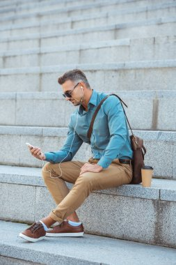 handsome middle aged man in sunglasses and earphones sitting on stairs and using smartphone
