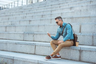 handsome stylish man in earphones and sunglasses sitting on stairs and using smartphone