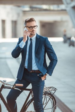 Handsome middle aged businessman in formal wear and eyeglasses sitting on bicycle and talking by smartphone stock vector