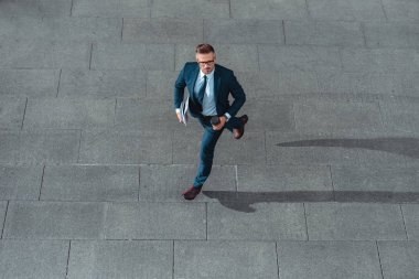 high angle view of middle aged businessman in formal wear holding coffee to go and running on street