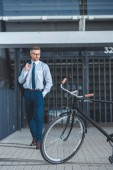 bicycle on street and middle aged businessman standing behind