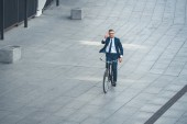 high angle view of middle aged businessman riding bicycle and showing victory sign