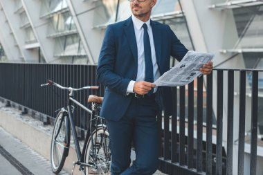 cropped shot of businessman in formal wear holding newspaper while standing with bike on street