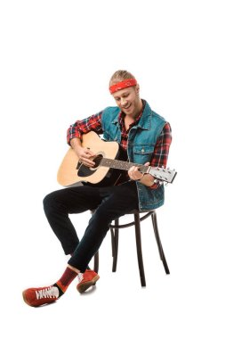 happy hipster man in denim vest playing on acoustic guitar isolated on white