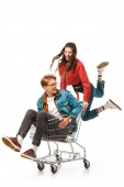 Fotografie excited hipster girl jumping and carrying shopping cart with boyfriend isolated on white