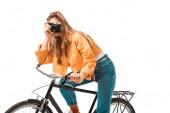 Fotografia ragazza giovane hipster attraente che si siede sulla bicicletta e tiro su macchina fotografica isolata su bianco
