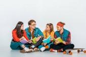 mladí studenti s longboard, čtení knih a hovořili spolu