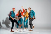 Fotografie cheerful stylish hipsters with beer bottles dancing together on grey