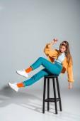 Photo beautiful young woman posing on stool on grey