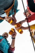 Fotografie bottom view of happy friends clinking with beer bottles together