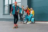 boldog fiatal meg gördeszka és kerékpár szórakozás utcában