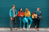 Fotografia elegante hipsters trascorrere del tempo con chitarra acustica e skateboard insieme sulla strada