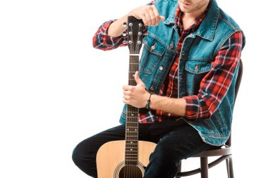 partial view of hipster man in denim vest sitting with acoustic guitar isolated on white
