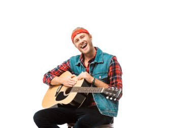 smiling hipster man in denim vest sitting with acoustic guitar isolated on white