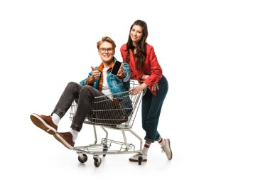 stylish male hipster in shopping cart showing smartphone with blank screen and doing thumb up while his girlfriend standing behind isolated on white