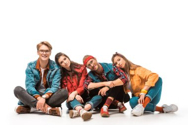 fashionable hipster friends sitting on floor and laying heads on each other shoulders isolated on white