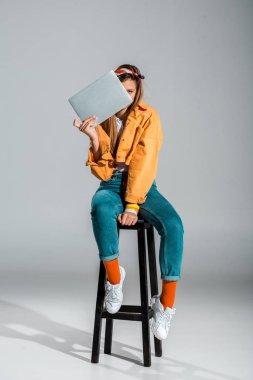 Stylish girl holding laptop while sitting on stool on grey stock vector