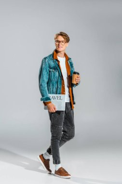 handsome hipster in denim jacket holding coffee to go and travel newspaper on grey