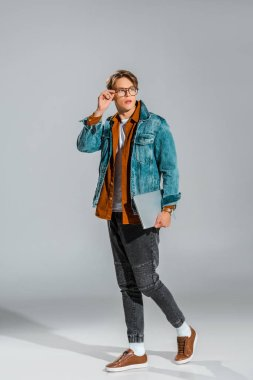 handsome stylish student posing in denim jacket with laptop on grey