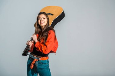 beautiful cheerful girl posing with acoustic guitar isolated on grey