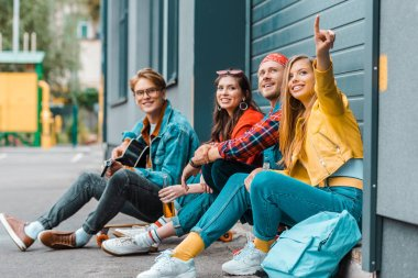 young friends spending time together on street while man playing guitar and woman pointing somewhere