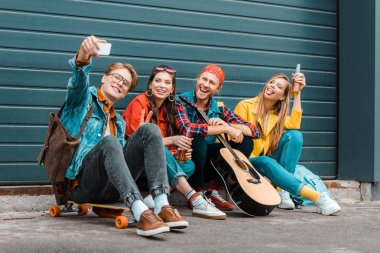 young friends with beer, skateboard and guitar taking selfie on smartphone