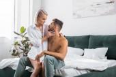 schöne junge Paar umarmt sitzend auf Bett zusammen