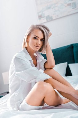 attractive young woman sitting on bed and looking at camera