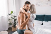 Fotografie smiling young man holding condom while embracing girlfriend in bedroom and looking at camera