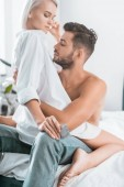 Fotografie passionate young couple with condom sitting on bed